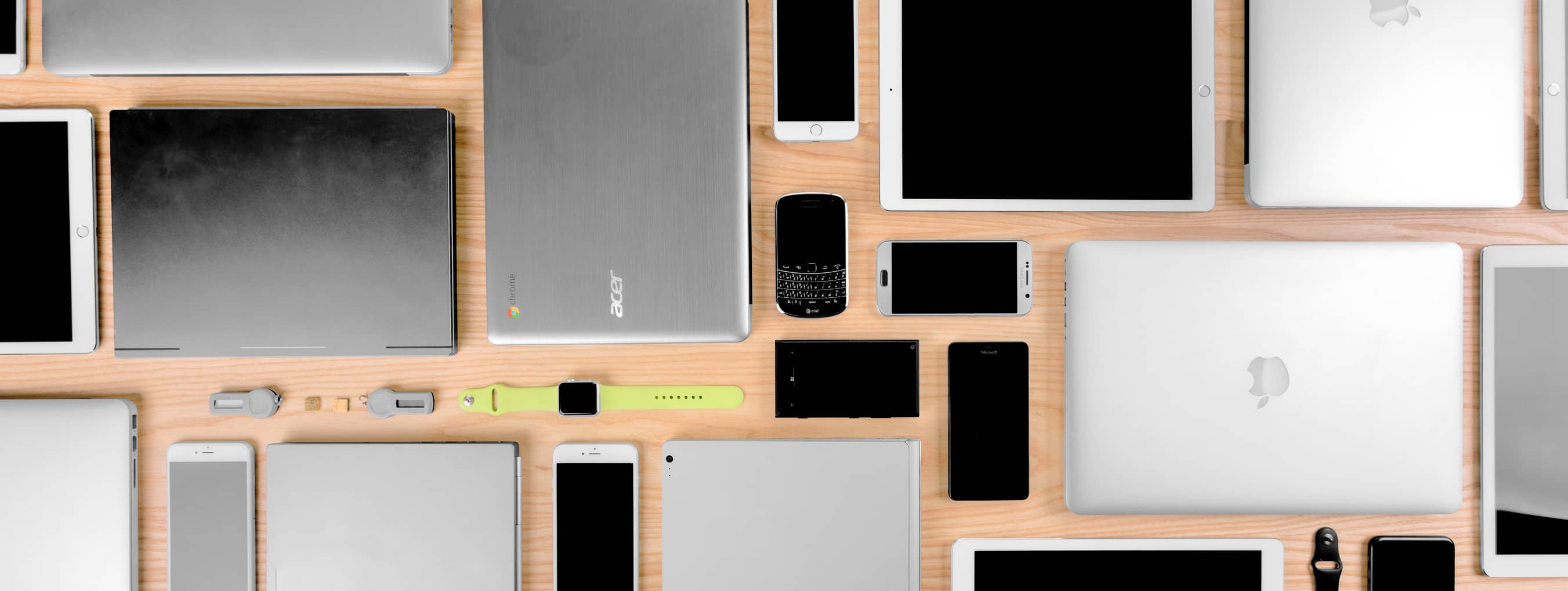 Image with a variety of devices, neatly arranged including laptop computers, smartphones, tablets and wearables.